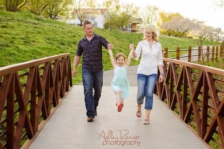 family on bridge swinging little girl