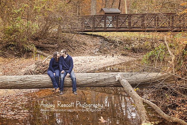 couple kissing on a fallen tree across water, fredericksburg va couple photographer