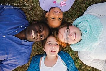 happy family laying in grass, fredericksburg va family photographer