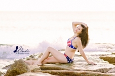 girl in patriotic bikini on rocks with wave