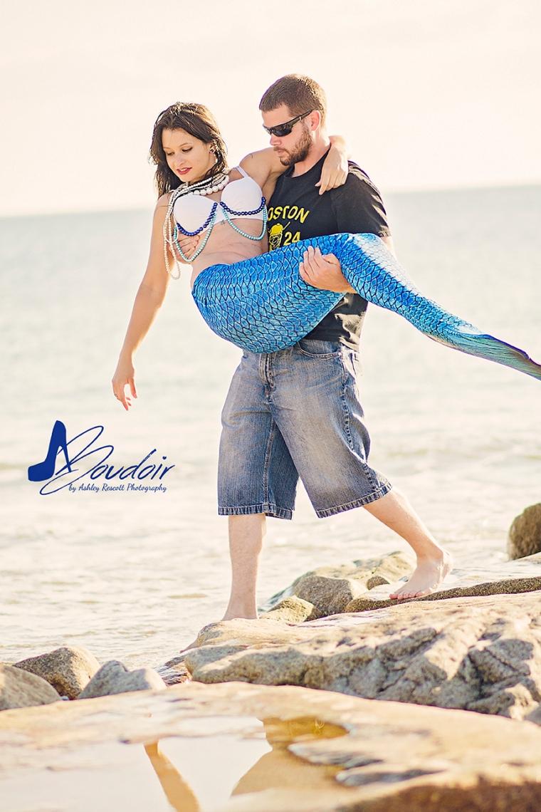 man carrying mermaid on beach