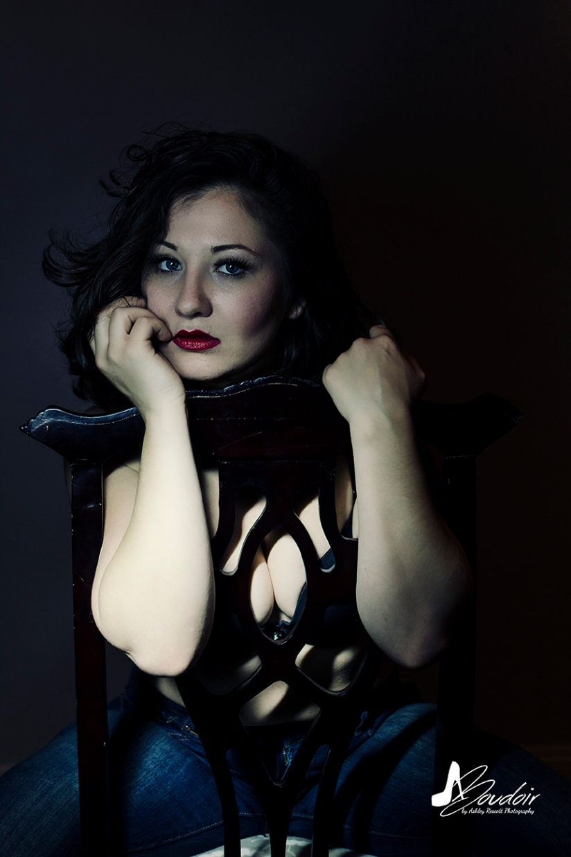 dark and moody portrait of woman in backwards queen anne chair