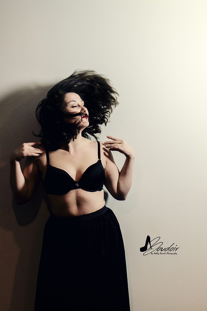 woman in black bra and skirt flipping hair