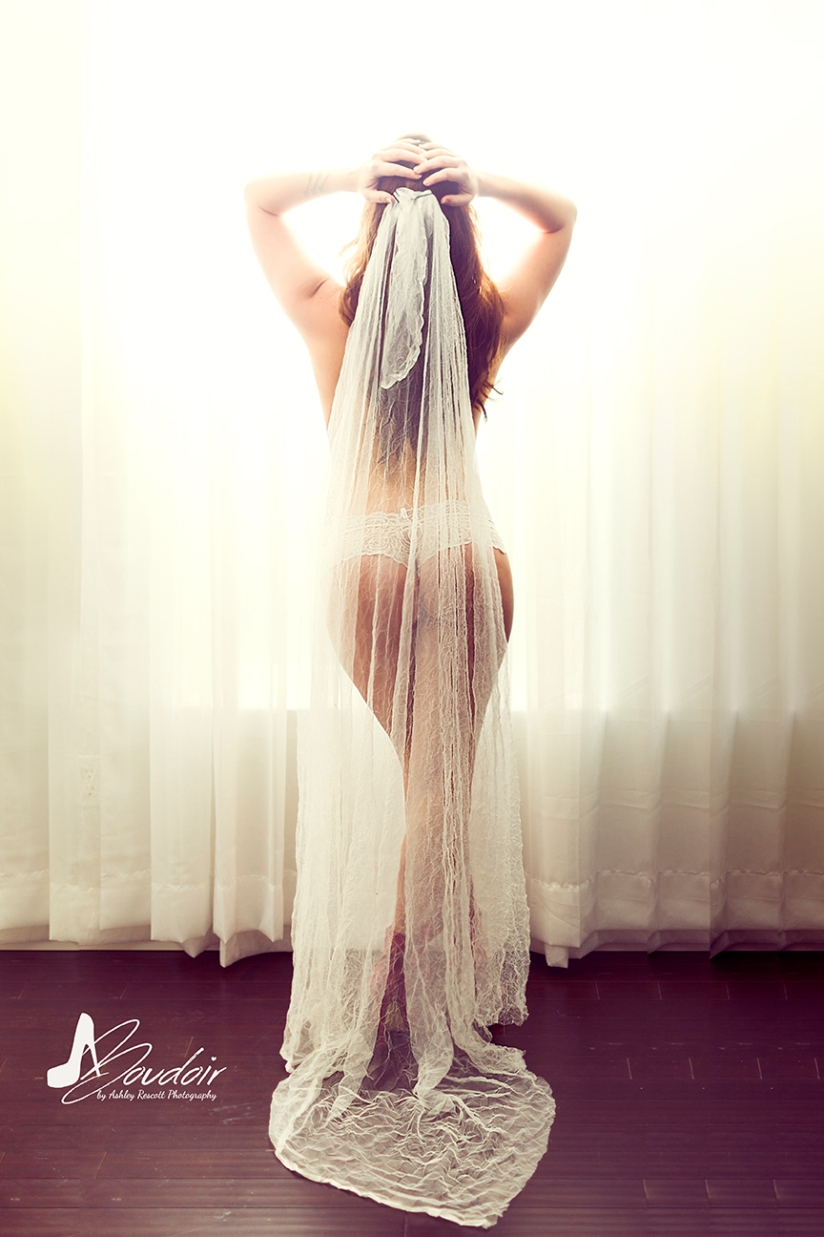 bride in veil in front of window