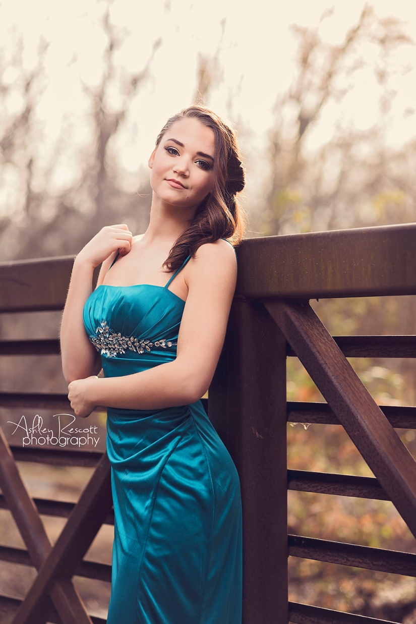 high school senior girl in turquoise prom dress on bridge