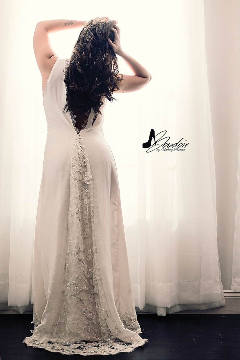 woman standing at window in white bridal dressing gown
