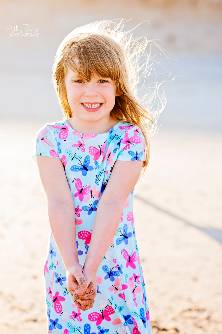 young girl on the beach wearing a butterfly dress