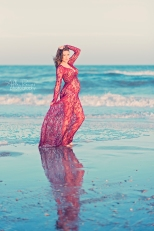 pregnant woman on beach in red lace dress
