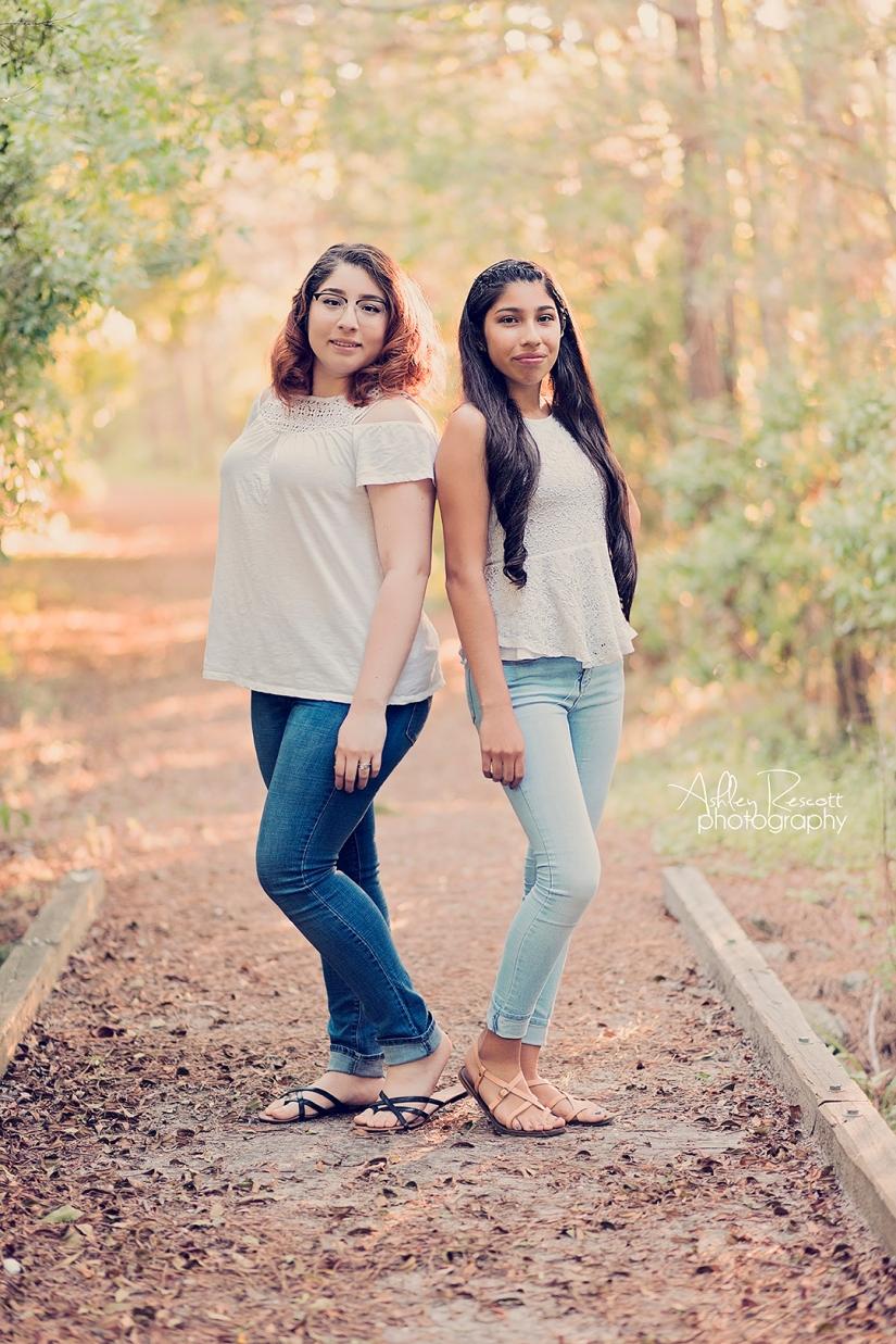 sisters standing on bridge in woods