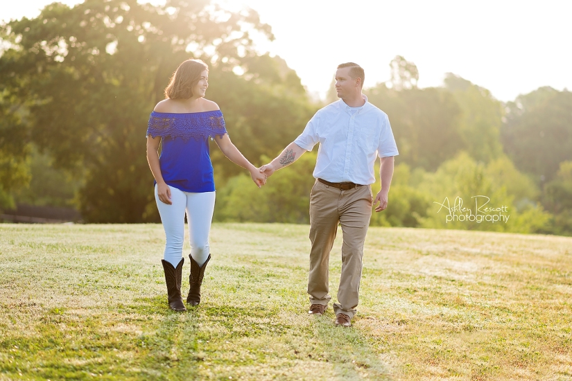 man and woman holding hands and walking on hill