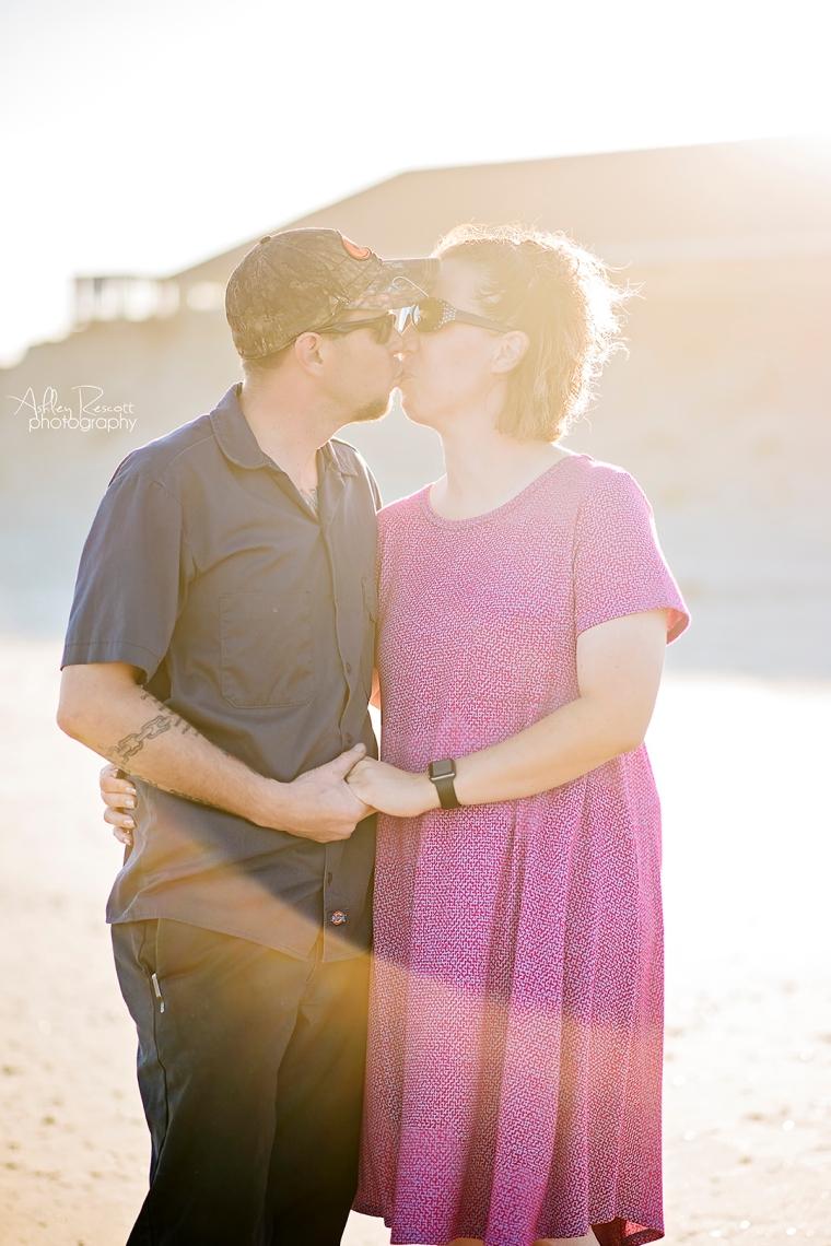 couple kissing on beach with sun flare