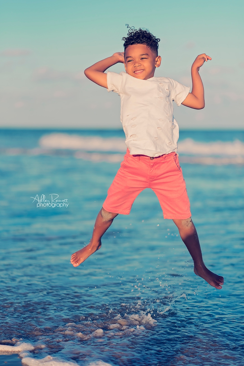 little boy jumping in ocean