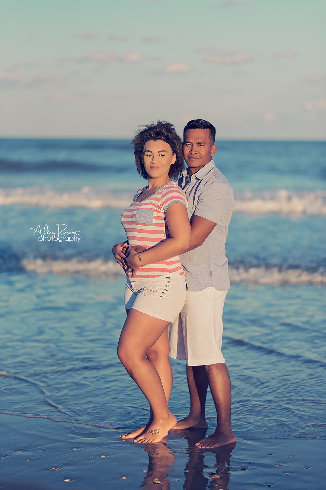 couple standing in water at beach