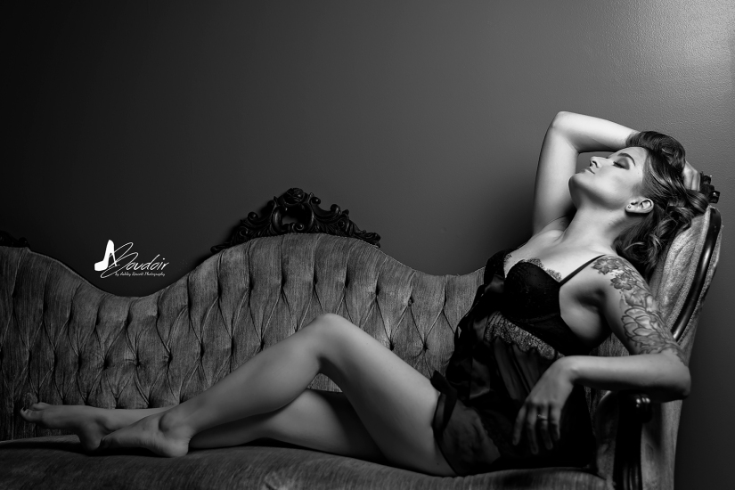black and white image of woman on couch in lingerie