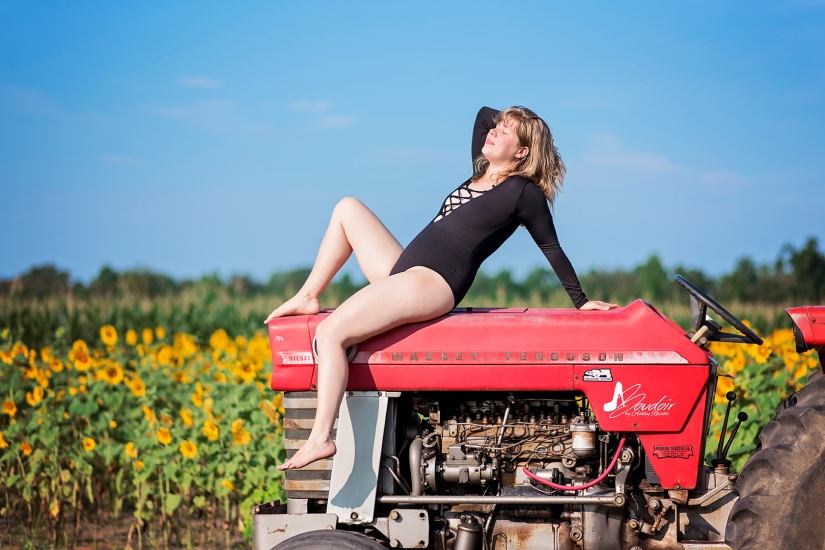 woman lounging on tractor in front of sunflowers