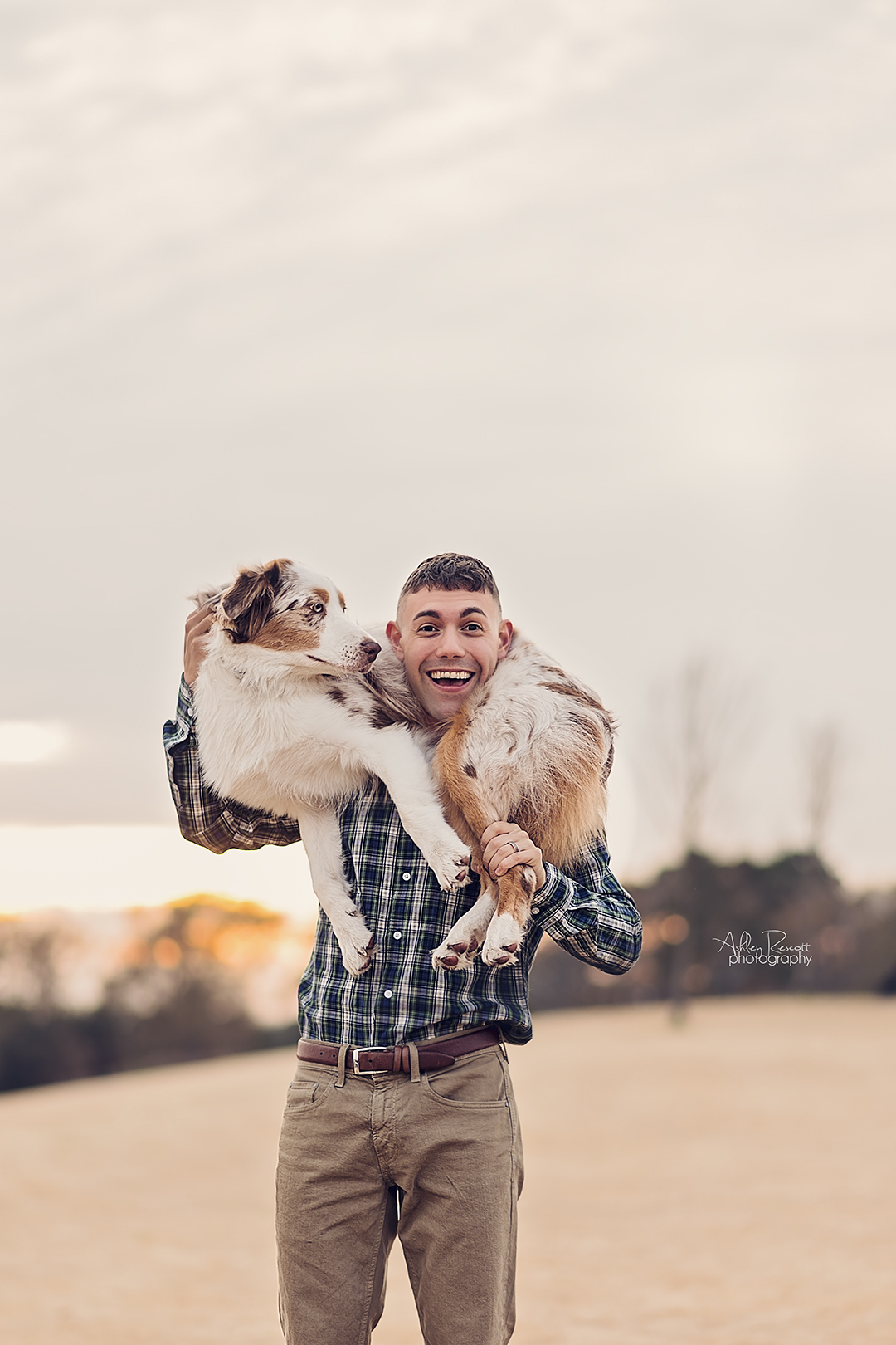 man holding dog on shoulders in field at sunset