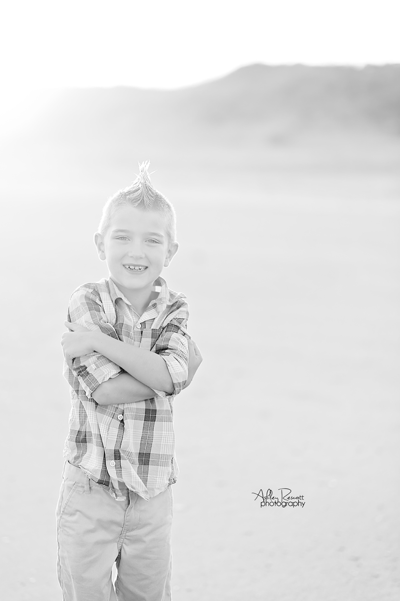 black and white photo of a boy on the beach