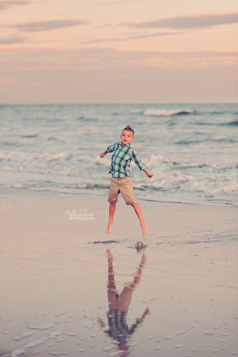 boy jumping in water on beach