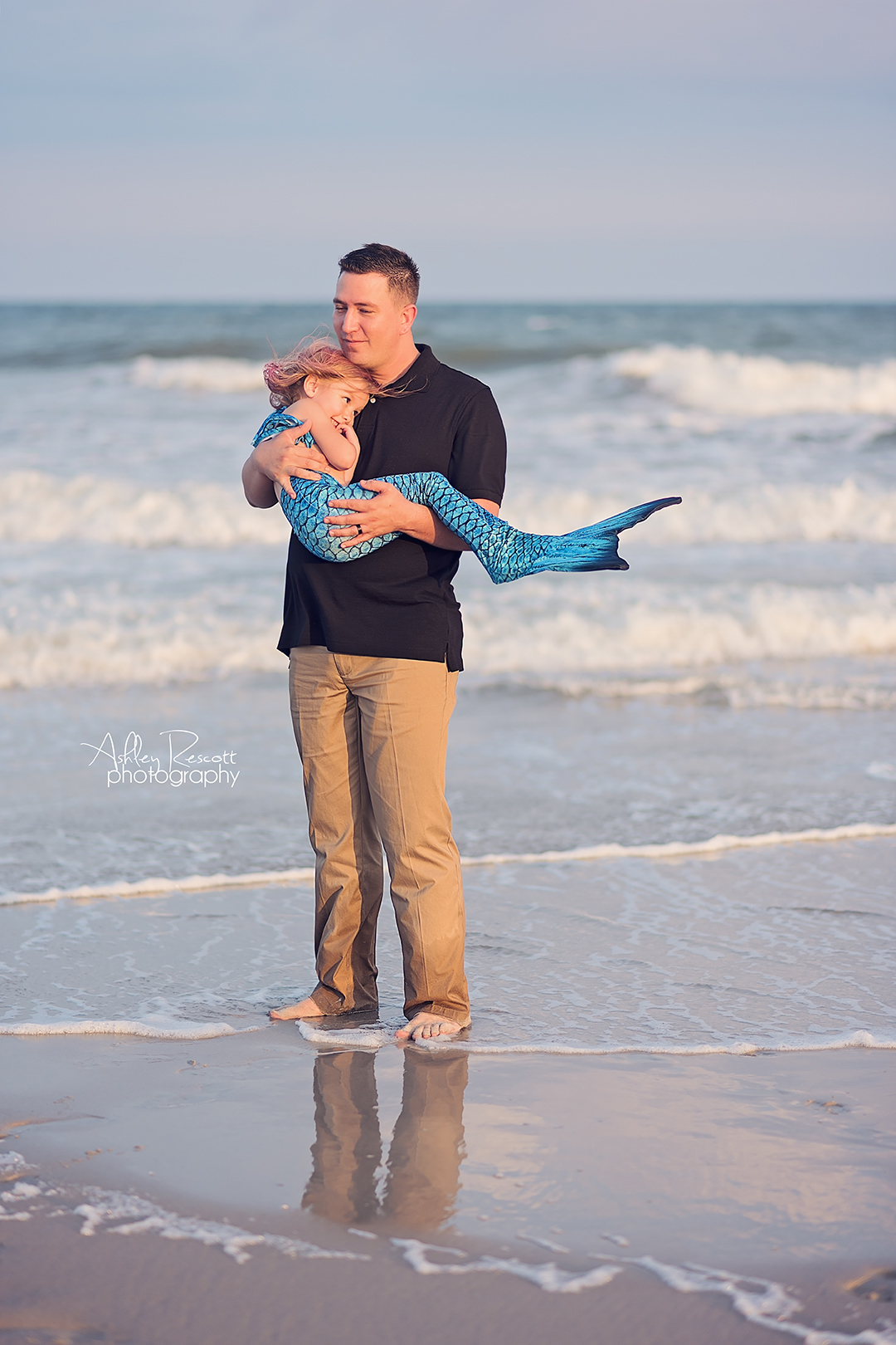 Dad and mermaid daughter in water at beach