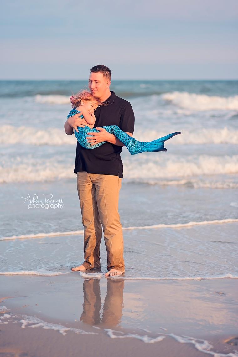 Dad and mermaid daughter in water at beach