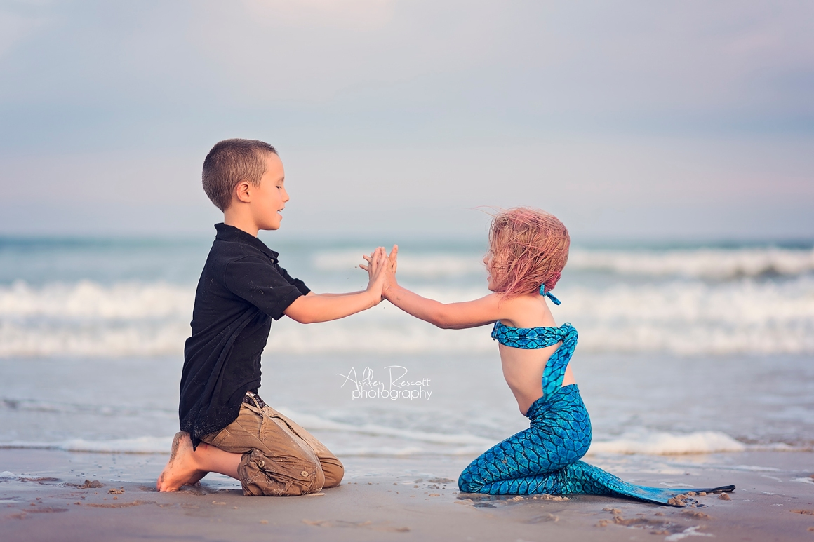 little boy playing pat a cake with mermaid on beach