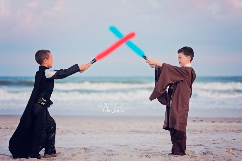 little boys star wars light saber battle on beach