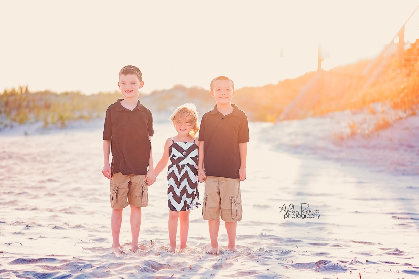 children in front of sand dunes on beach