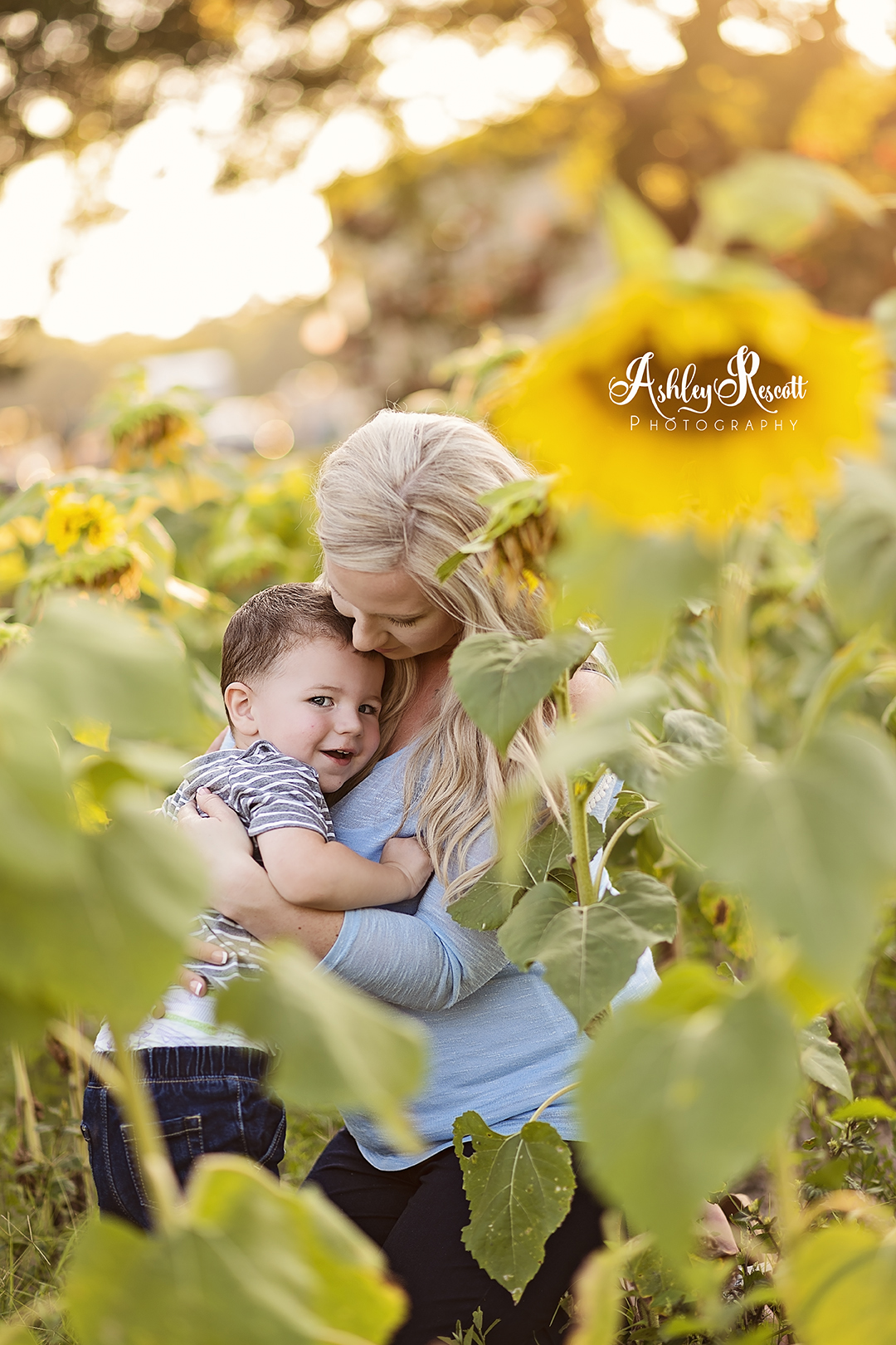 little boy cuddling mom in a sunflower field