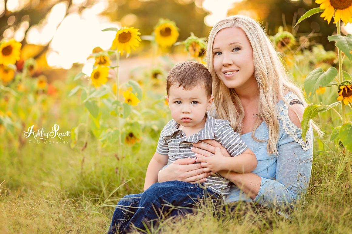 little boy cuddling mom in a sunflower field