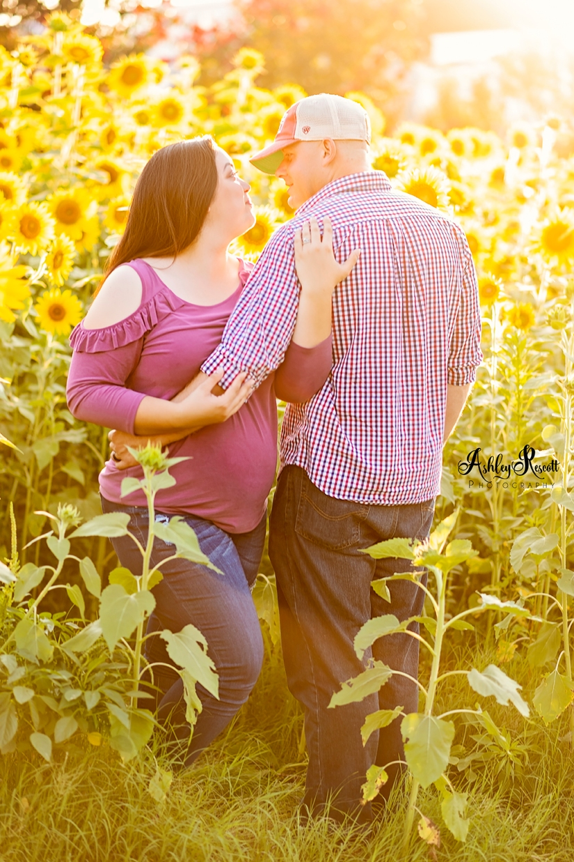 pregnant woman in sunflower field with husband