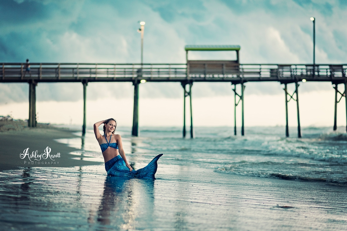 mermaid in front of pier on beach with stormy skies