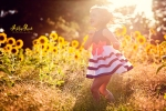 little girl jumping in sunflower field