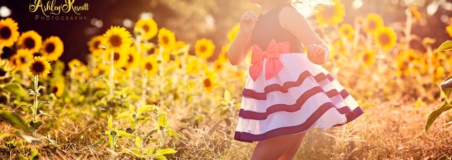 little girl jumping in sunflower field