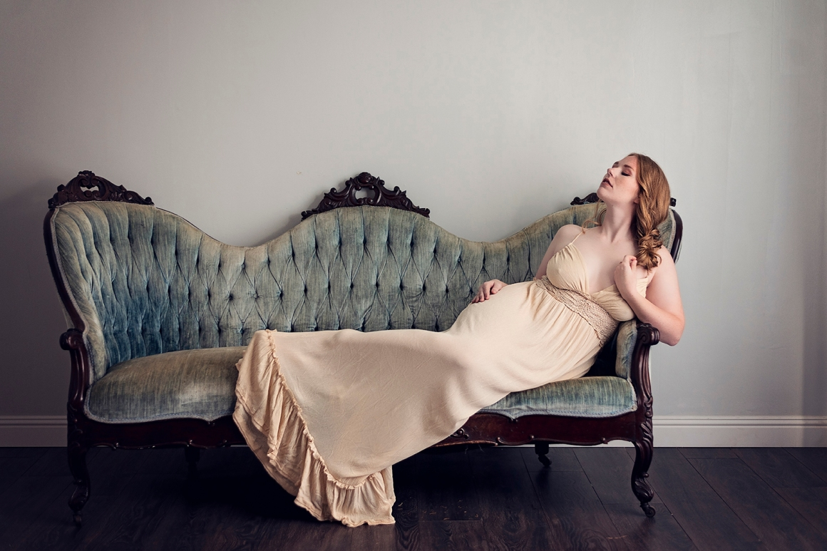 woman in beige dress on blue victorian couch