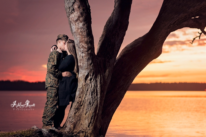 couple kissing & leaning on tree at sunset next to water