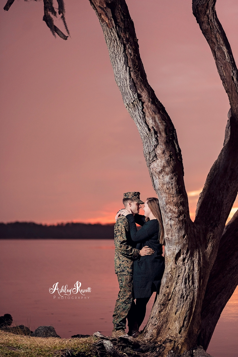 couple leaning on tree at sunset next to water