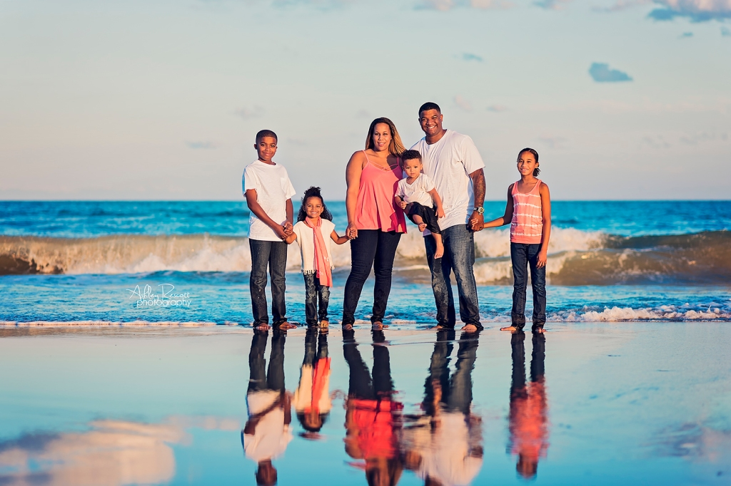 Family standing at water's edge at beach with a reflection of them in the water