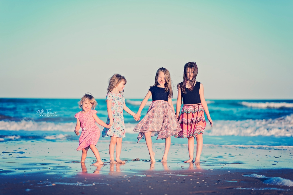 Sisters standing at water's edge on beach
