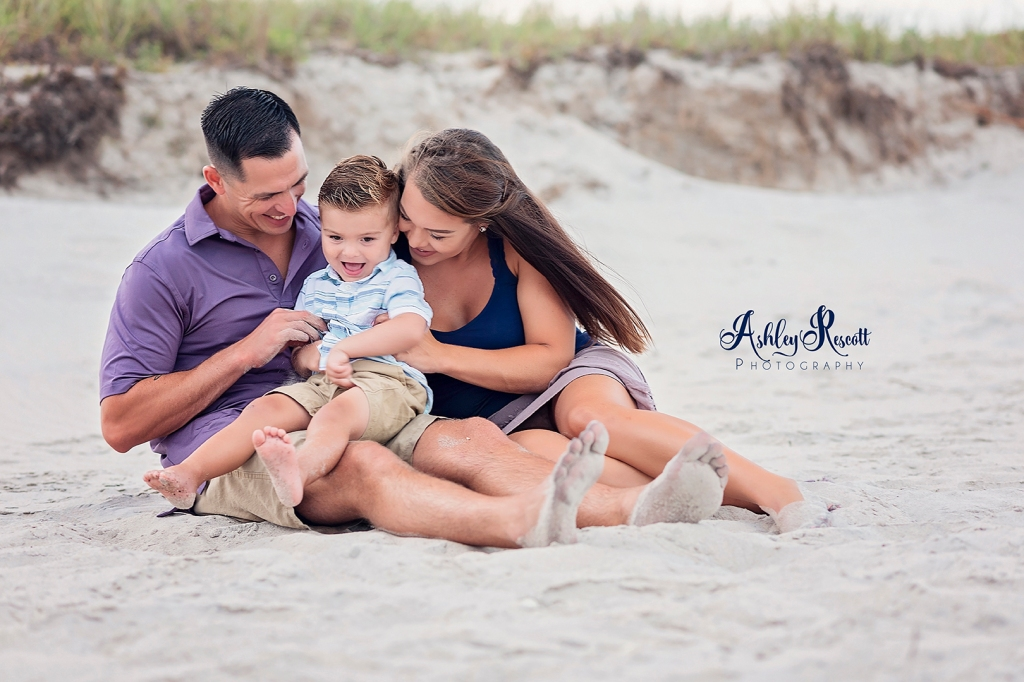 family having a tickle fight on the beach