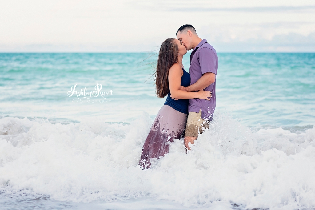 couple kissing while standing in waves at beach at sunset