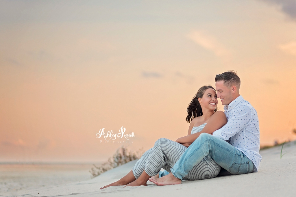 couple cuddling on beach during sunset