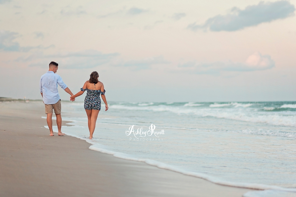 couple walking down the beach holding hands at sunset