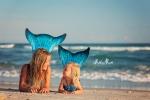 sisters in mermaid tails on beach
