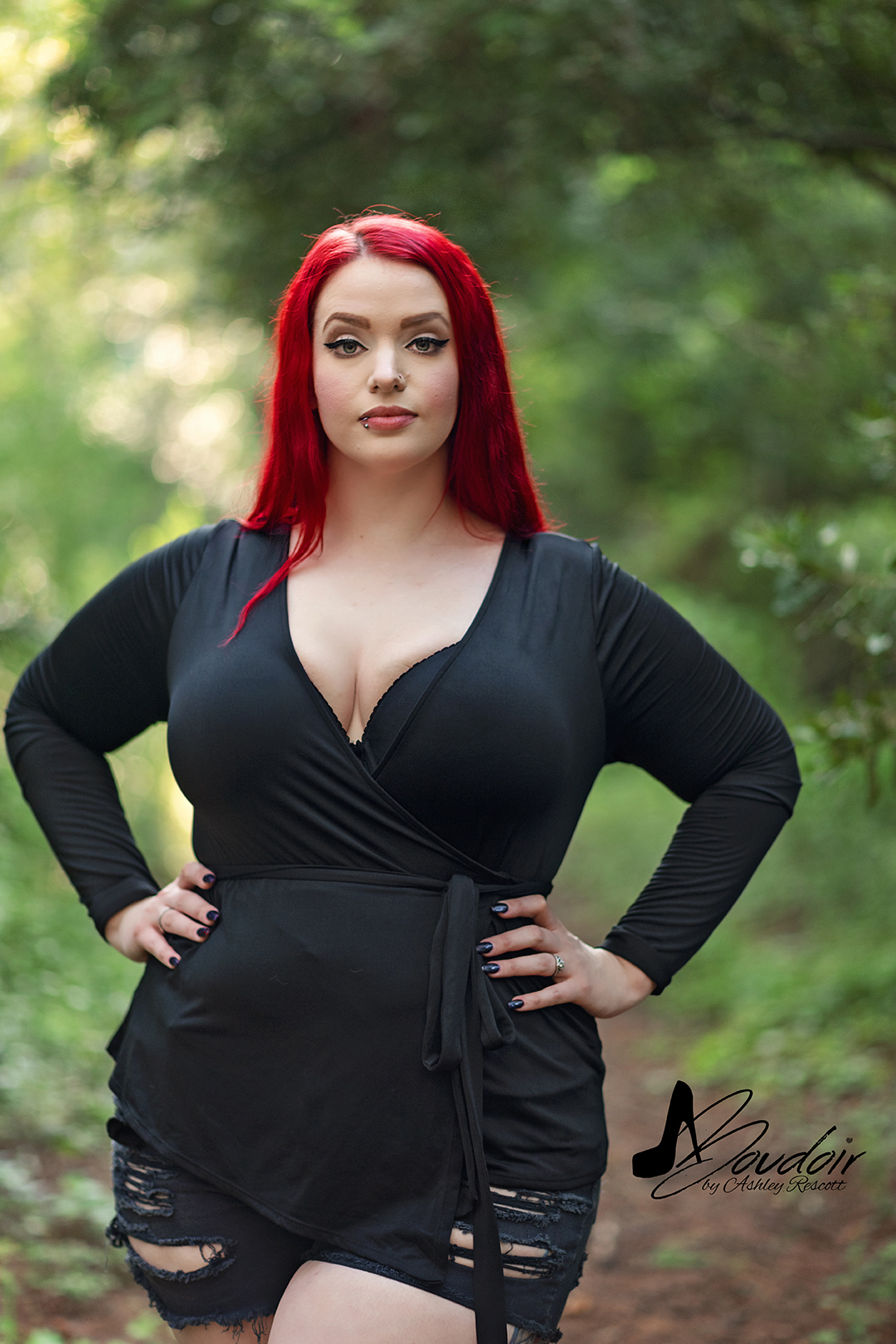 red haired woman standing in woods during her boudoir session.