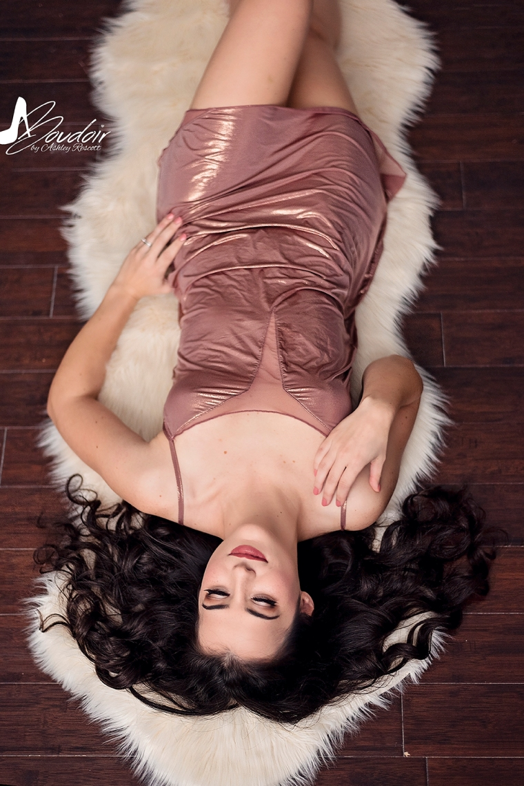 boudoir image of woman lying on sheepskin rug