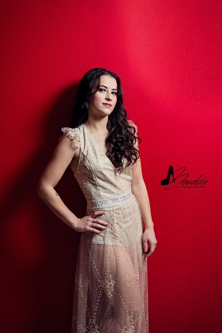 boudoir image of woman in sparkle dress leaning against red wall