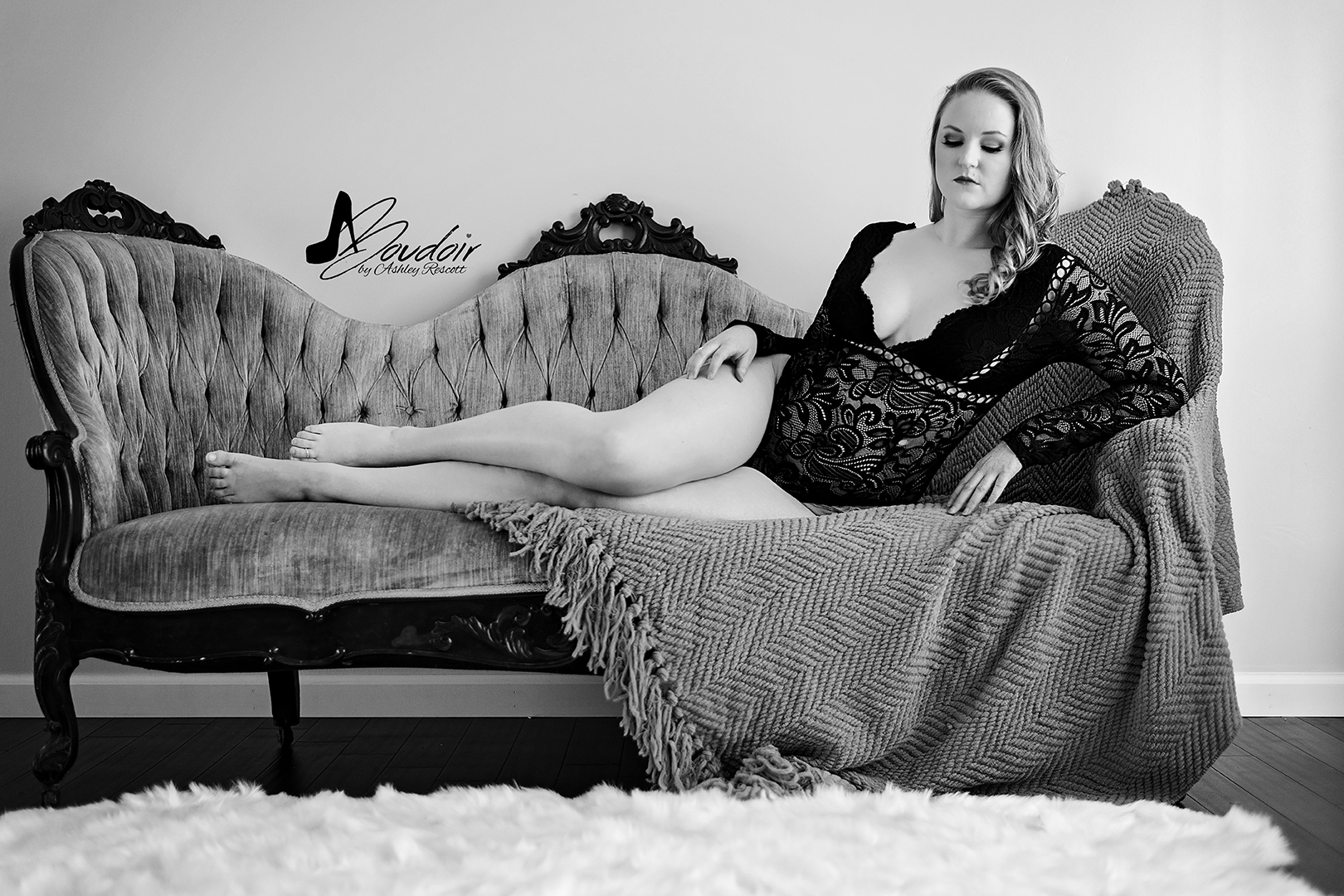 black and white image of woman lounging on couch
