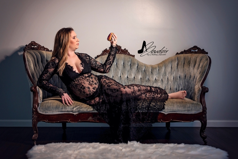 woman in black lace dress lying on couch looking at donut