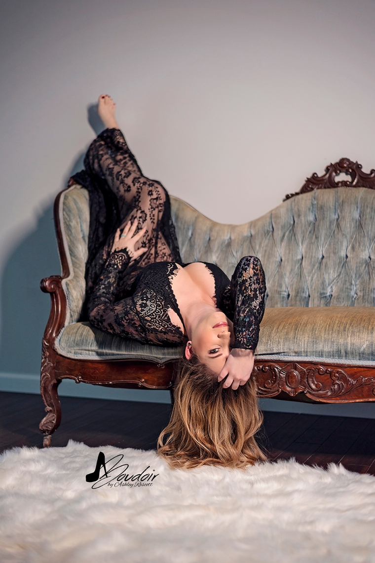 woman in lace dress lying upside down on couch