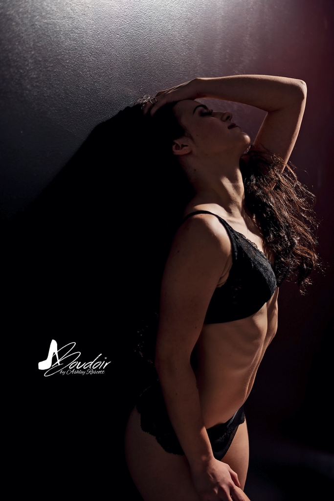 boudoir image of woman leaning against black wall